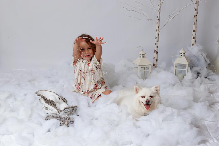Little girl and her white dog american eskimo at City Tails Pet Boarding